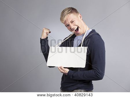 Excellent news: Successful excited man shouting while holding white blank signboard with space for text isolated on grey background.