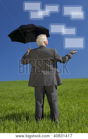Network concept photograph of a businessman standing in a green field with an umbrella holding out his hand and looking at graphic screen boxes