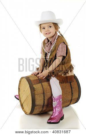 Ein glücklich Vorschule Cowgirl gebietsübergreifenden ein rustikales Holz Fass, als handele es sich um ein Pferd.  Auf einem weißen backgro