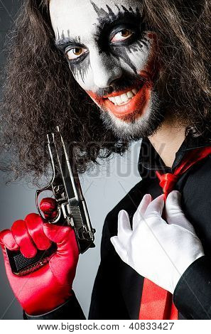 Evil clown with gun in dark room