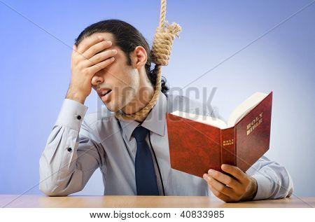 Businessman reading bible before hanging himself