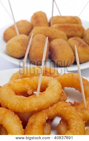 closeup of some plates with spanish croquettes and calamares a la romana, squid rings, served as tapas