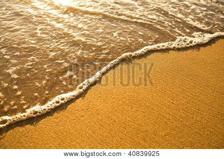 Beach sand texture. Soft wave of the sea.