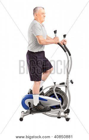 Full length portrait of a mature sporty man exercising  on a cross trainer isolated on white background