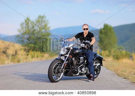 Man posing on a costume made motorcycle on the road