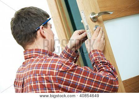 Carpintero manitas masculino en la instalación de la cerradura de puerta interior de madera