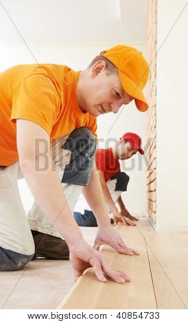 Two parquet carpenter workers installing wood board during flooring work