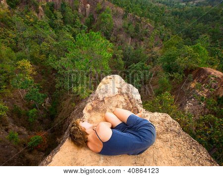 Picture of loneliness - young girl lying on top of the rock in the canyon.
