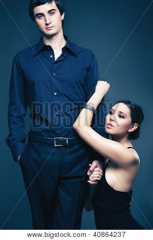 Vertical image of a beautiful woman pleading her boyfriend to stay with her, isolated on black