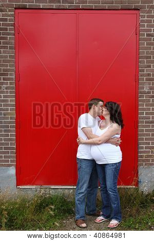 Maternity photos of a couple with red doors as a background - 8 months pregnant