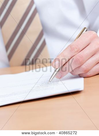 Sitting at the table business man writing in the notebook