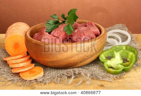Raw beef meat in bowl with vegetables on wooden table on brown background