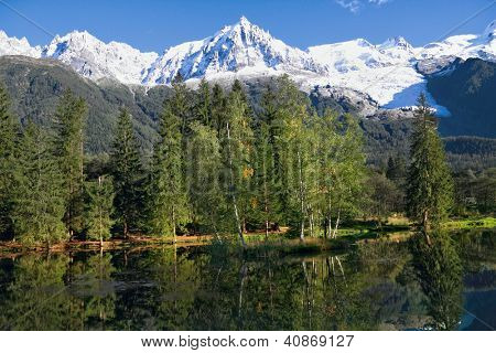 Reflections of snow-capped peaks and coastal trees in city park pond.  Chamonix - a famous ski resort in the French Alps
