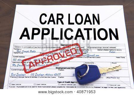 Approved car loan application form and key on desktop