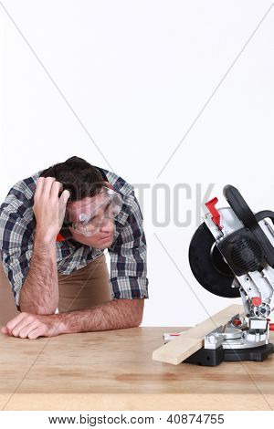 A perplexed carpenter looking at a circular saw.