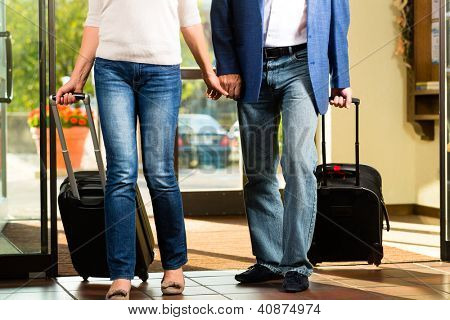 Senior man and woman - married couple - arriving at Hotel with their luggage