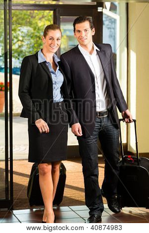 Business people arriving at Hotel with suitcases