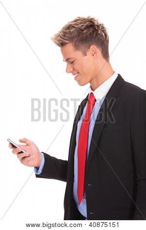 Young business man standing on white background reading a text message on his smartphone