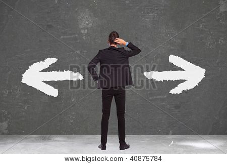 back of an undecided young business man standing with his hand on his head and thinking waht to do