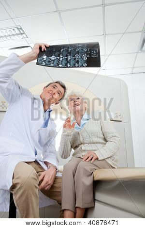 Mature male radiologist with senior female patient looking at x-ray