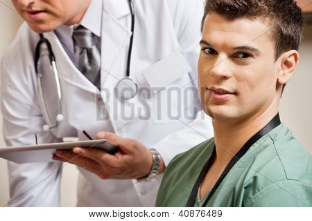 Portrait of male technician with doctor holding digital tablet in background