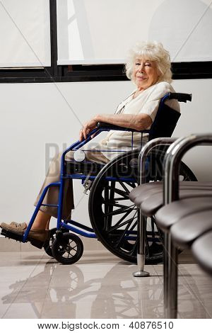 Portrait of an elderly woman on wheelchair in hospital lobby