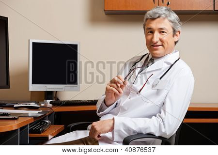 Portrait of mature male doctor sitting in front of computer desk at clinic