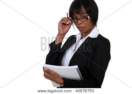 portrait of black businesswoman with glasses lowered holding notebook