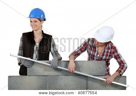 two craftswomen measuring a wall