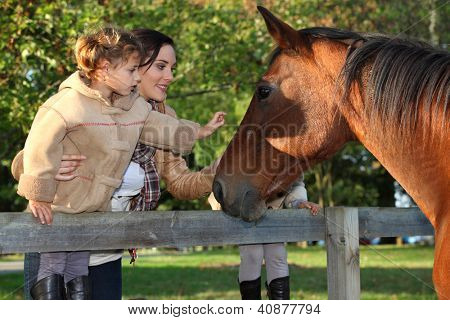 Mother and daughter next to horse