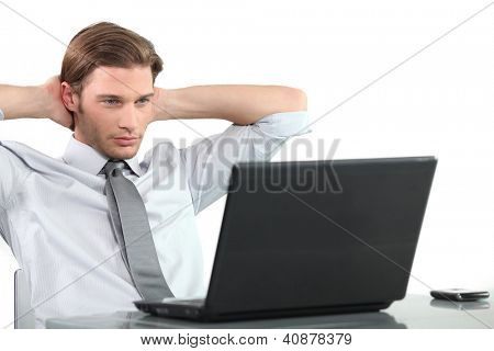 Young businessman at laptop with arms behind head.