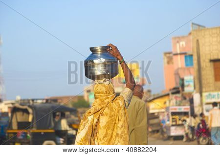Woman Carrys A Pot Of Water On Her Hat