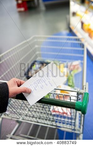 Hand, holding a shopping list with day to day groceries and other necessities, whilst pushing a shopping cart through a supermarket