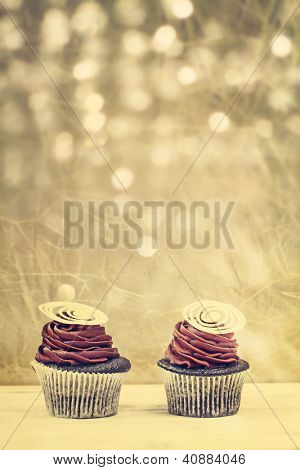 two chocolate cupcake with chocolate mousse cream icing on grunge wooden background with copy space over silver background with lights