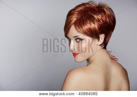 bela jovem de cabelos vermelhos, vestindo o penteado de corte pixie curto no fundo do estúdio