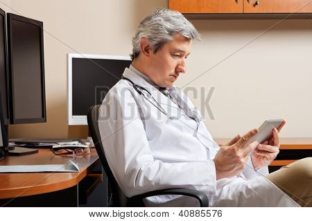 Grave médico masculino maduro olhar digital tablet, sentado por mesa