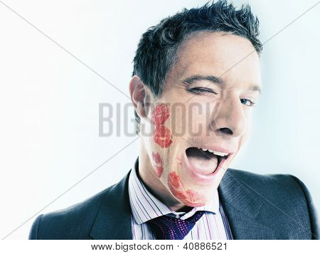 Flirtatious businessman with lipstick marks over his face