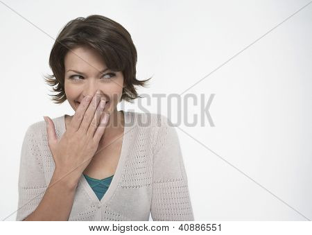 Shy woman covering mouth with hand over white background
