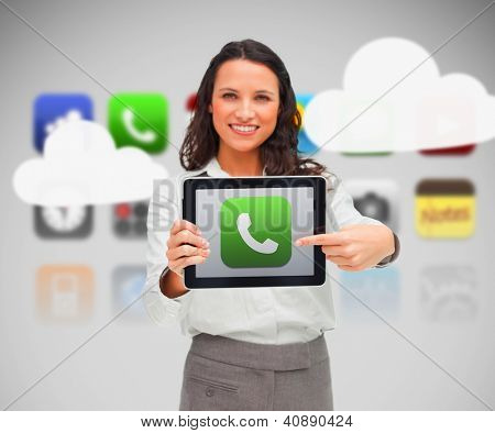 Woman holding tablet pc pointing to phone symbol on background of various phone applications and clouds