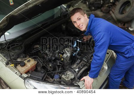 Portrait of male mechanic with flashlight examining car engine