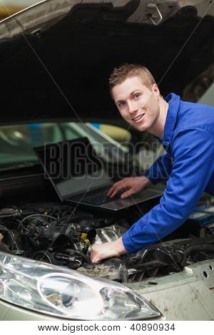 Portrait of happy car mechanic with laptop checking engine