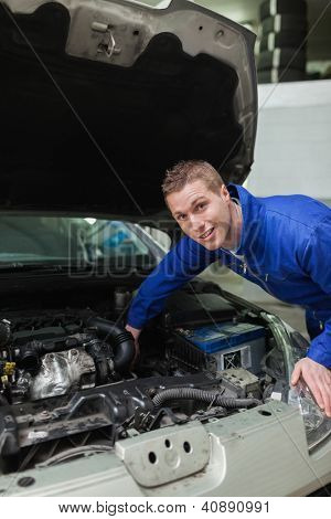 Portrait of male mechanic working under bonnet of car