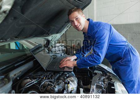 Portrait of happy male auto mechanic using laptop