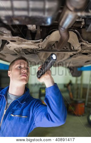 Male mechanic with flashlight examining under car