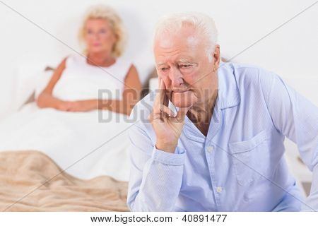 Discouraged old couple in the bedroom