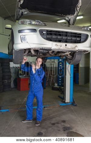 Full length portrait of male mechanic working under raised car in workshop