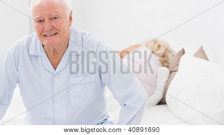 Old man sitting while woman sleeping on the bed