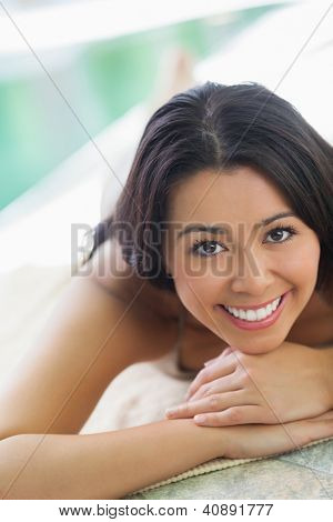 Smiling woman lying on towel by pool