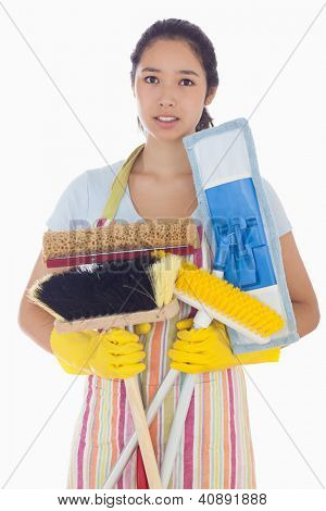 Frowning woman in apron and rubber gloves holding brushes and mops