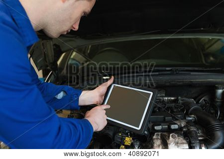 Auto mechanic by car with open hood using digital tablet